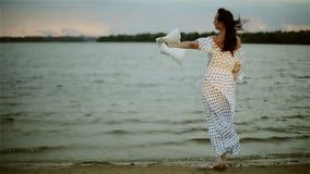 Eine mittlere Greisin in einem langen Sommerkleid, das auf dem Strand steht, weg von ihrem Hut sich setzt und den Wind genießt stock video footage