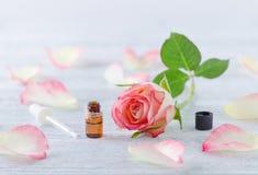 Eine ml-Flasche mit ätherischem Öl, natürlicher rosafarbener Blüte und Pipette auf der Weinlese hölzern Lizenzfreies Stockfoto
