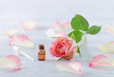 Eine ml-Flasche mit ätherischem Öl, natürlicher rosafarbener Blüte und Pipette auf der Weinlese hölzern Lizenzfreies Stockbild