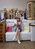 Eine moderne Frau, die auf einem Sofa nahe bei ihren Einkaufstaschen auf einem Shophintergrund sitzt Ein Mädchen, das auf einem s Lizenzfreie Stockfotos