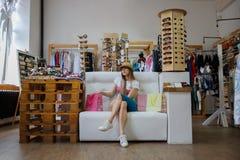 Eine moderne Frau, die auf einem Sofa nahe bei ihren Einkaufstaschen auf einem Shophintergrund sitzt Ein Mädchen, das auf einem s Stockbild