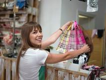 Eine moderne Frau, die Käufe von Kleidung in einem Speicher auf einem unscharfen Hintergrund tut Eine Frau mit Einkaufstaschen in Lizenzfreies Stockfoto
