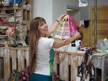 Eine moderne Frau, die Käufe von Kleidung in einem Speicher auf einem unscharfen Hintergrund tut Eine Frau mit Einkaufstaschen in Stockfoto