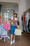 Eine moderne Frau, die Käufe von Kleidung in einem Speicher auf einem unscharfen Hintergrund tut Eine Frau mit Einkaufstaschen in Stockbilder