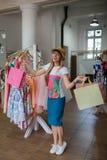 Eine moderne Frau, die Käufe von Kleidung in einem Speicher auf einem unscharfen Hintergrund tut Eine Frau mit Einkaufstaschen in Lizenzfreie Stockfotografie