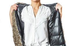 Eine moderne Frau in einer Jacke, in einem weißen Hemd und in der Hose hält ihre Hände in einer modischen Geste für ihre Jacke Stockfoto