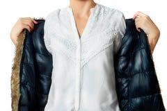 Eine moderne Frau in einer Jacke, in einem weißen Hemd und in der Hose hält ihre Hände in einer modischen Geste für ihre Jacke Stockfotos