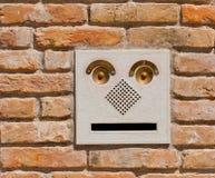 Eine moderne Wechselsprechanlagentürklingelplatte auf dem alten Ziegelstein wal lizenzfreie stockfotos