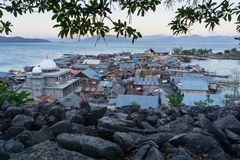 Eine Moschee auf einer kleinen Insel n?rdlich der Insel von Flores Indonesien mit den Bl?ttern als Vordergrund und durch blaue Me stockbild