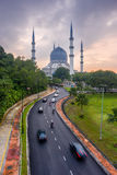 Eine Moschee und ein bewölkter Sonnenaufgang mit den Autos, die Straßen weitergehen Stockfotos