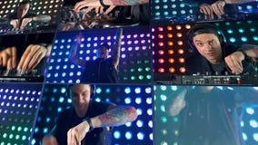 Eine multiscreen Montage von einem DJ experimentiert mit verschiedenen Griffen an seinem Mischer 4K stock video