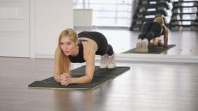 Eine muskulöse Sportlerin führt eine Planke in durch stock footage