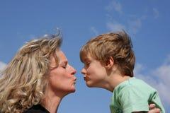 Eine Mutter, die ihrem Sohn einen Kuss gibt Lizenzfreie Stockfotografie