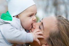 Eine Mutter, die ihren netten kleinen Sohn umarmt Lizenzfreie Stockfotografie