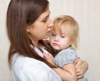Eine Mutter hält ein krankes Mädchen an. lizenzfreies stockbild