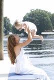 Eine Mutter hält ihre Tochter playfully in der Luft an Stockbild