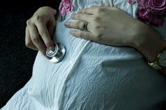 Eine Mutter hört auf ihren Bauch unter Verwendung eines Stethoskops Stockfoto