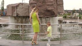 Eine Mutter mit einem kleinen Sohn ist, spielend gehend und im Park nahe dem Brunnen stock footage