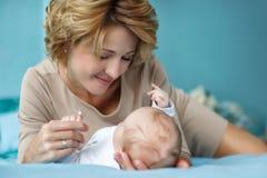Eine Mutter mit einem neugeborenen Sohn, der auf dem Bett liegt Lizenzfreies Stockbild