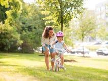 Eine Mutter mit Tochter in einem sonnigen Stadtpark Lizenzfreies Stockfoto