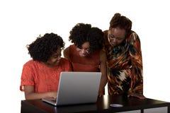 Eine Mutter oder ein Lehrer, die einen Computer mit 2 Jugendlichen betrachten Lizenzfreie Stockfotos