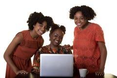 Eine Mutter oder ein Lehrer, die einen Computer mit 2 Jugendlichen betrachten Stockfotografie