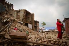 Eine Mutter und ein Kind außerhalb eines Erdbebens ruinierten Haus in Bhaktap stockbild