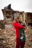 Eine Mutter und ein Kind außerhalb eines Erdbebens ruinierten Haus in Bhaktap stockfotos