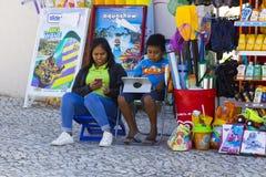 Eine Mutter und ein Sohn, der ihren Handy und Tablette, wie sie, verwendet außerhalb ihres kleinen Shops in Albuferia in Portugal Lizenzfreie Stockfotografie