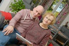 Eine Mutter und ihr erwachsener Sohn, die eine digitale Tablette betrachten Lizenzfreies Stockfoto