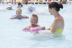 Eine Mutter und zwei Töchter schwimmen in einem Gemeinschaftspool lizenzfreies stockbild