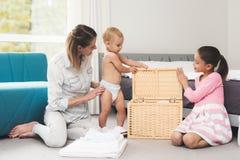 Eine Mutter von zwei Kindern hat Spaß mit Kindern während der Hausreinigung Sie sind in einem hellen Raum und setzen Kleidung in  stockfotos