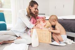 Eine Mutter von zwei Kindern hat Spaß mit Kindern während der Hausreinigung Sie sind in einem hellen Raum und setzen Kleidung in  lizenzfreie stockfotos