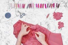 Eine Näherin, die eine Spitzeblume zu einem Kleid mit einem geraden Stift befestigt Stockfoto