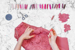 Eine Näherin, die eine Spitzeblume zu einem Kleid mit einem geraden Stift befestigt Stockbild