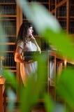 Eine nachdenkliche Frau mit den Büchern durch die grünen Blätter Stockbild