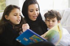 Eine nahöstliche Familie, die zusammen ein Buch liest Stockfotografie