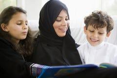 Eine nahöstliche Familie, die zusammen ein Buch liest Stockfoto
