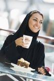 Eine nahöstliche Frau, die eine Mahlzeit genießt Stockbild