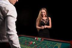 Eine Nahaufnahme auf der Rückseite des Croupiers in einem weißen Hemd, Bild der grünen Kasinotabelle mit Rouletten und Chips, Rei lizenzfreies stockfoto