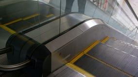 Eine Nahaufnahme der beweglichen Schritte der Rolltreppe Männer klettern die elektrische Treppe aufwärts Schauen Sie und Atem des stock footage