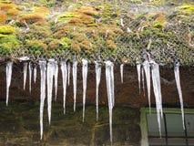 Nahaufnahme der Eiszapfen, die von einem Dach hängen. Stockbild