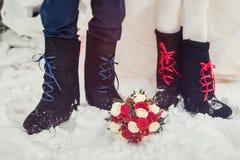 Eine Nahaufnahme der Füße der Braut und des Bräutigams in den Filzstiefeln auf Schneehochzeitsblumenstrauß Zubehör für eine stili Lizenzfreie Stockbilder