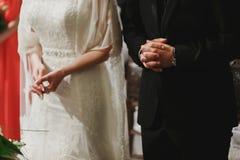 Eine Nahaufnahme der Hände des Hochzeitspaares, während sie in der Kirche beten Lizenzfreie Stockfotografie