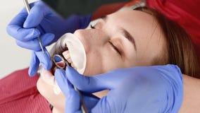 Eine Nahaufnahme des Gesichtes des M?dchens wird von einem zahnmedizinischen Pr?fer mit seinem Mund ?berpr?ft, der offen sind und stock video footage