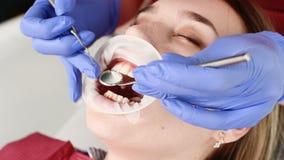 Eine Nahaufnahme des Gesichtes des M?dchens wird von einem zahnmedizinischen Pr?fer mit seinem Mund ?berpr?ft, der offen sind und stock footage