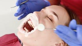 Eine Nahaufnahme des Gesichtes des M?dchens wird von einem zahnmedizinischen Pr?fer mit seinem Mund ?berpr?ft, der offen sind und stock video