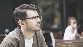 Eine Nahaufnahme des Mannes in den Brillen draußen hörend am Café Lizenzfreie Stockfotografie