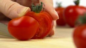 Eine Nahaufnahme des Schnitts einer Tomate mit einem Messer stock video footage