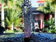 Eine Nahaufnahme, Detail eines vertikalen sprudelnden Brunnens, der von unterhalb beleuchtetes Purpurrotes ist stockbilder